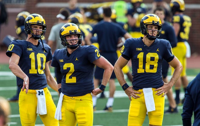 Michigan quarterbacks Dylan McCaffrey (10), Shea Patterson (2) and Brandon Peters (18) stand during a break in a preseason open practice session by the NCAA college football team at Michigan Stadium in Ann Arbor, Mich., Sunday, Aug. 26, 2018. Patterson transferred from Mississippi and has been named the starter. (AP Photo/Tony Ding)
