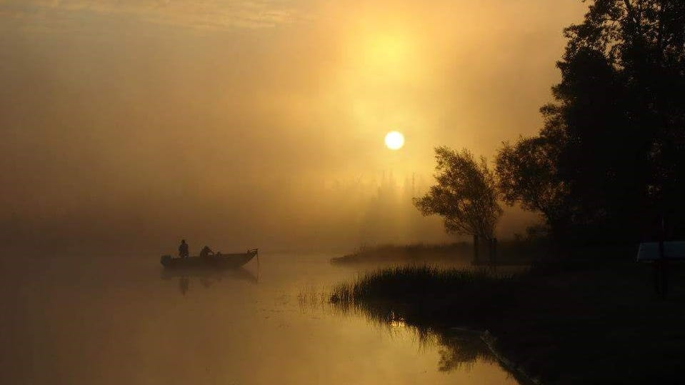 """FOUR-SEASON FUN WINNER: """"Misty Fishing Morning,"""" by Diane Kanneth of Highland Park. One morning in Commerce Township, she got up early and headed down to Proud Lake, trying not to drop her coffee, granola bar and camera.  """"In that struggle,"""" she said, """"I lifted my camera in the direction of the boaters that captured my attention. The photo I quickly snapped without much expertise or thought reminds me of that one beautiful morning."""""""