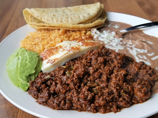 The Esperanza plate at Tres Reynas contains beef cooked in a dark chile sauce with cactus, served with beans and rice, fried fresh cheese, tortillas and avocado.