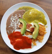 Huevos Divorciados--two eggs with green and red sauce served with beans, rice, fried fresh cheese and avocado.