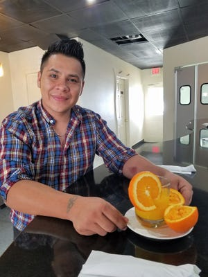 Marco Leon with a glass of orange juice. When you order it at Tres Reynas, they squeeze it for you.