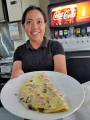 If you're not feeling adventurous, Tres Reynas offers plenty of American cafe dishes, such as this omelet held by Susanti Sarworini.