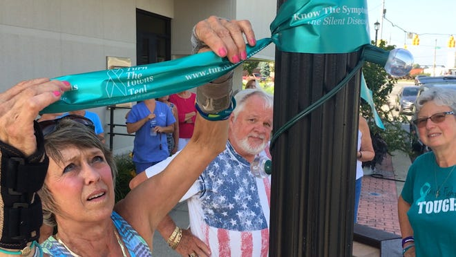 """Patti Tucker of Fremont, a member of the Ovarian Cancer Connection, hangs teal ribbons downtown for """"Turn the Towns Teal,"""" a national campaign to promote awareness of ovarian cancer, its symptoms, and risk factors."""