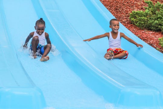 Gannon Wilkerson, 3, and his brother Jimmy, 4, of Fort Myers race down a slide at  Sun Splash Waterpark.