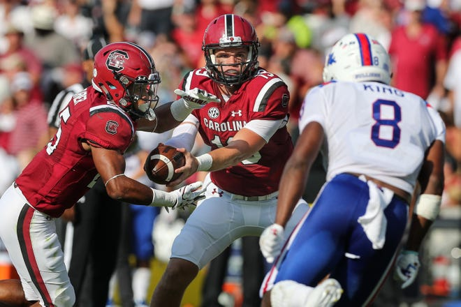 South Carolina quarterback Jake Bentley (19) hands off to running back A.J. Turner (25) in front of Louisiana Tech Bulldogs safety DaMarion King (8) during this 2017 matchup at Williams-Brice Stadium.