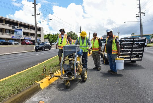 Guam Department of Public Works employees paint a median using a striping machine on Marine Corps Drive in Tamuning in this Aug. 27, 2018, file phot0.