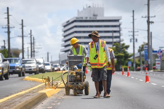 Guam Department of Public Works employees paint a median using a striping machine on Marine Corps Drive in Tamuning, Aug. 27, 2018. The crew will continue to install pavement marking on Route 1 between Citibank in east Hagåtña and the Micronesia Mall in Dededo as part of the Guam Transportation Program's ongoing road improvement projects.