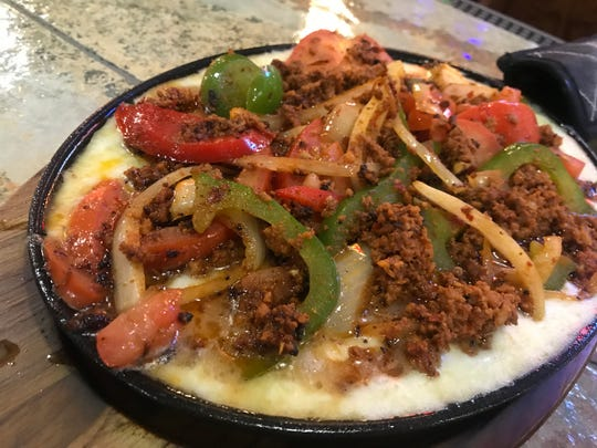 Choriqueso is a generous serving of melted cheese topped with sautéed chorizo, peppers and onions at Loco Mexican Restaurant & Cantina in the Fall Creek Place neighborhood of Indianapolis.