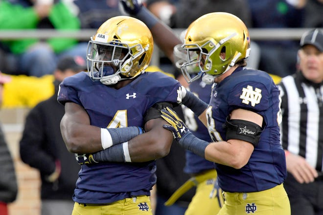Oct 28, 2017; South Bend, IN, USA; Notre Dame Fighting Irish linebacker Te'von Coney (4) and linebacker Greer Martini (48) celebrate after a sack in the second quarter against the North Carolina State Wolfpack at Notre Dame Stadium. Mandatory Credit: Matt Cashore-USA TODAY Sports