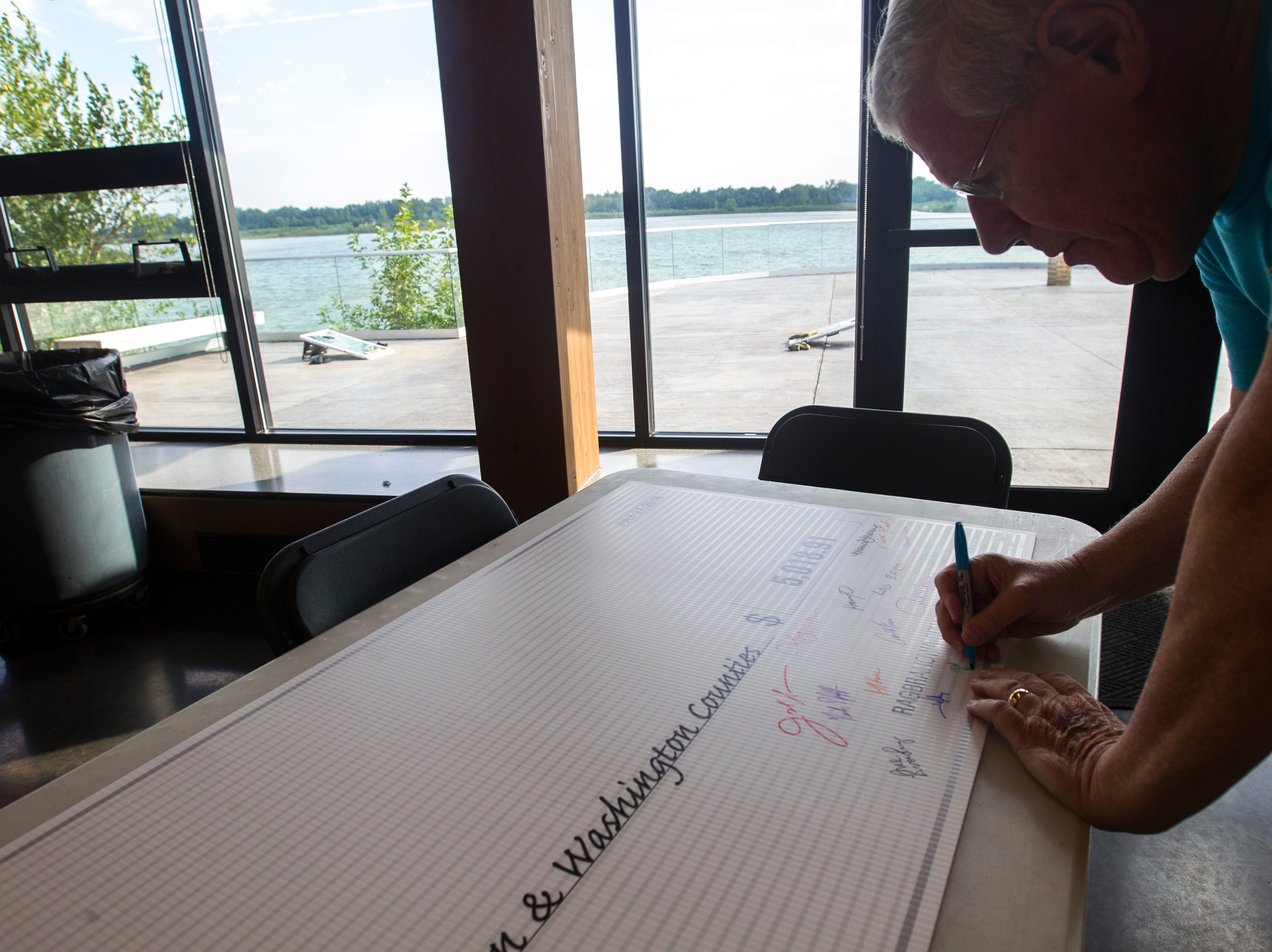 Iowa State Sen. Bob Dvorsky (D-Coralville) signs a check for the United Way of Johnson and Washington Counties during an event for Iowa City RAGBRAI volunteers on Monday, Aug. 27, 2018, inside the Park Lodge at Terry Trueblood Recreation Area in Iowa City.