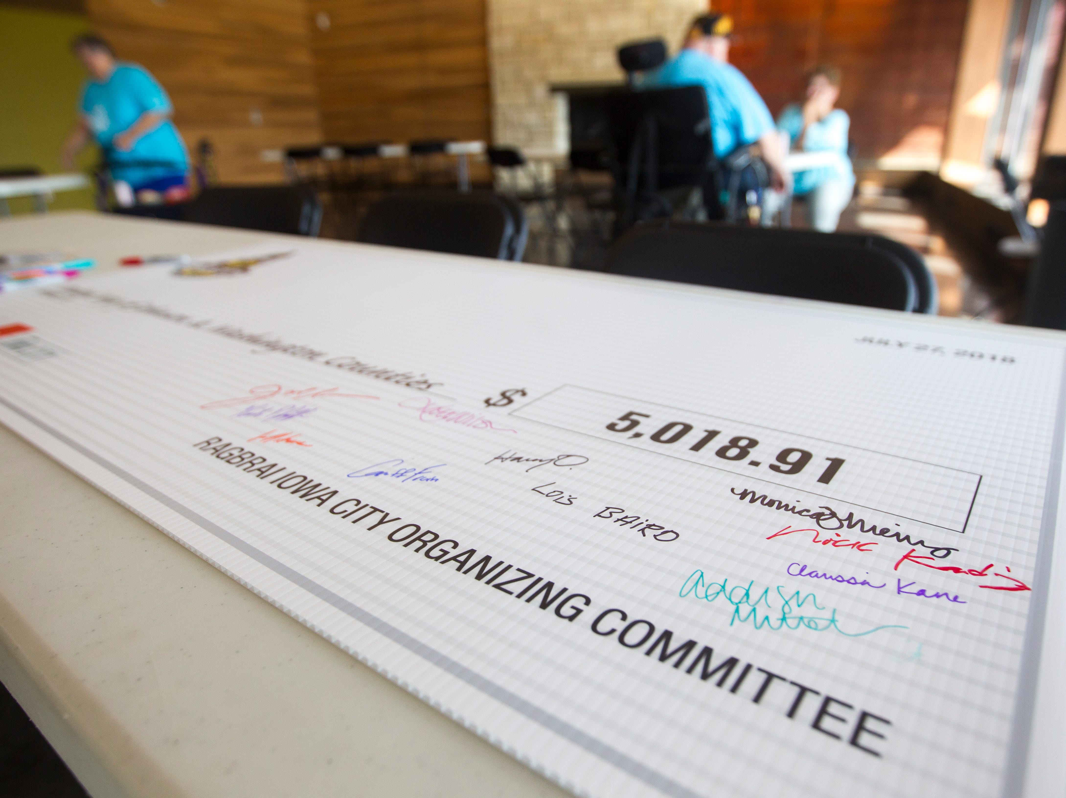 A check to the United Way of Johnson and Washington Counties sits out to be signed by guests during an event for Iowa City RAGBRAI volunteers on Monday, Aug. 27, 2018, inside the Park Lodge at Terry Trueblood Recreation Area in Iowa City.