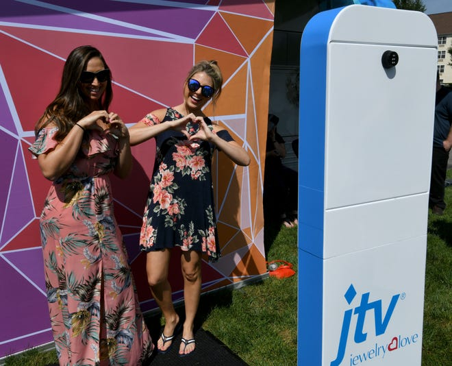Jewelry Television employees Christina Yanez and Lissa Daigle use the selfie booth as JTV unveiled its Jewelry Love Tour bus to employees on Friday, August 24, 2018 at the Parkside Drive headquarters. The bus will hit the road to visit some of its biggest fans around the South this fall.