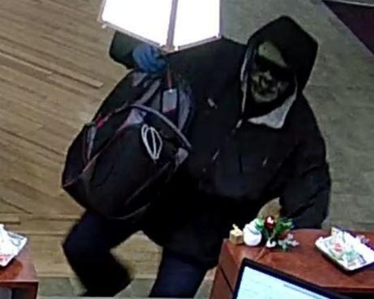"""The FBI is searching for information that may aid in the arrest of the """"Too Tall Bandit,"""" seen here robbing Citizens National Bank in Knoxville."""