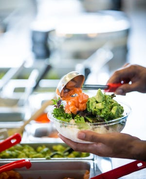 Guests at Poke Bros. restaurant choose from a rice base, vegetables, meat, sauce and toppings when building a poke bowl.