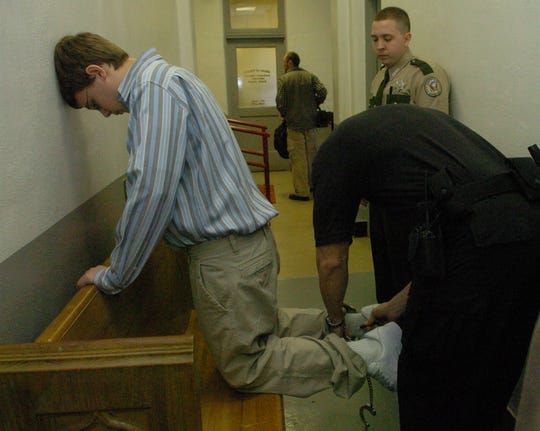 A teenage Kenny Bartley kneels on a bench as Campbell County sheriff's deputy John Long removes shackles from his ankles as Deputy Dustin Hatfield keeps watch. Bartley killed an administrator and wounded two others in 2005 at Campbell County Comprehensive High School.