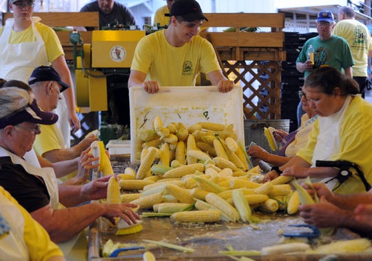 Photo by Matthew Berry/Eagle-Gazette Dozens of ears of sweet corn are dumped onto a table to be husked and cleaned last year at the Millersport Sweet Corn Festival in Millersport. This year's festival will run from Wednesday through Saturday and feature national country acts Dylan Scott and Mark Chestnut.