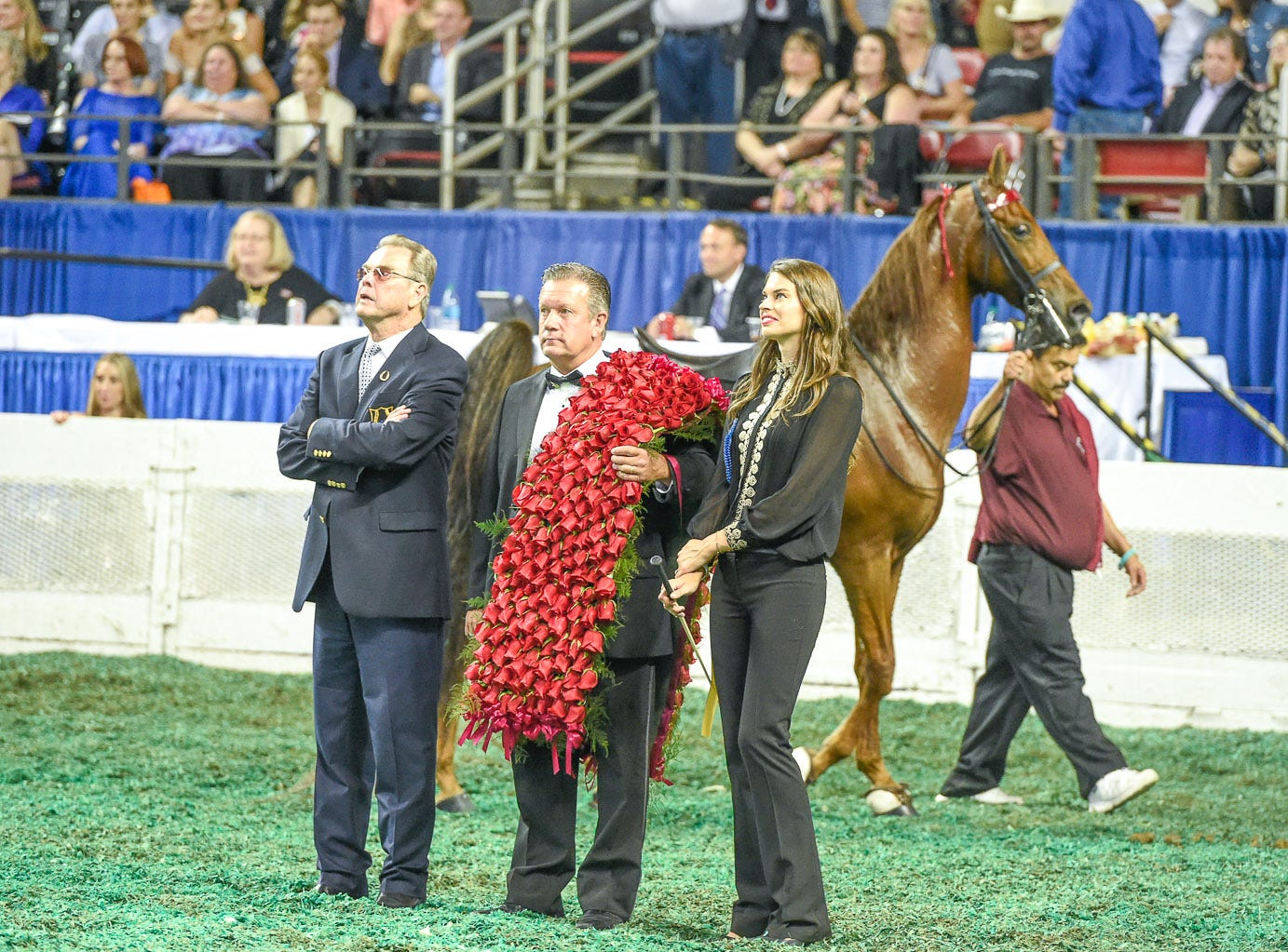 Kelly Lockhart and trainer Larry Hodge look on while Daniel Lockhart give his victory speech while The Daily Lottery walks with caretaker before victory pass after winning the 5 Gaited World's Grand Championship