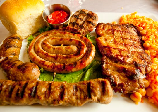 The Four Seasons' mixed pork grill consists of  (clockwise from top center) kufta, a pork chop, a kerbache, nadenitsa, and in the center of the plate, a karnache. The meal is accompanied by a home-made Bulgarian dinner roll and saffron rice with chick peas, right. The sauce, top center left, is lyutenitsa, made with tomatoes, peppers, onions, garlic, and Bulgarian spices. Chef Valentin Todorov makes all sausages and cheeses by hand (he says he has 15 patents on cheeses.) 
