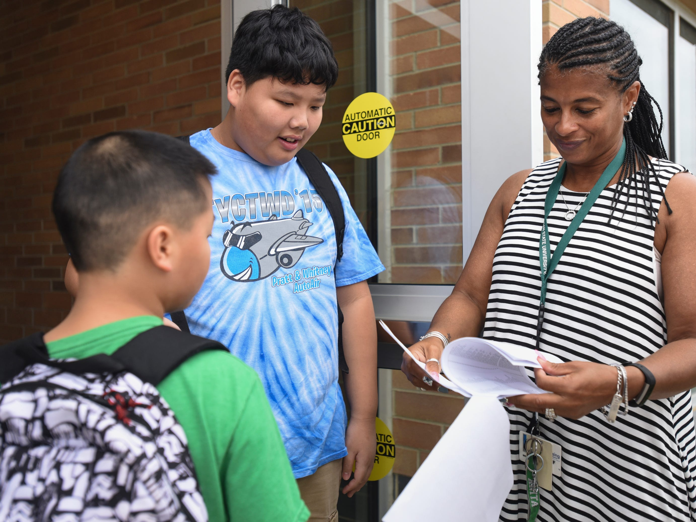 Pattengill teacher Anita Alston-Palmore helps direct fifth graders Yue Yang Pheng, middle, and Yengwa Yang to their classes Monday morning, Aug. 27, 2018, at the newly-renovated Pattengill Biotechnical Magnet School in Lansing.