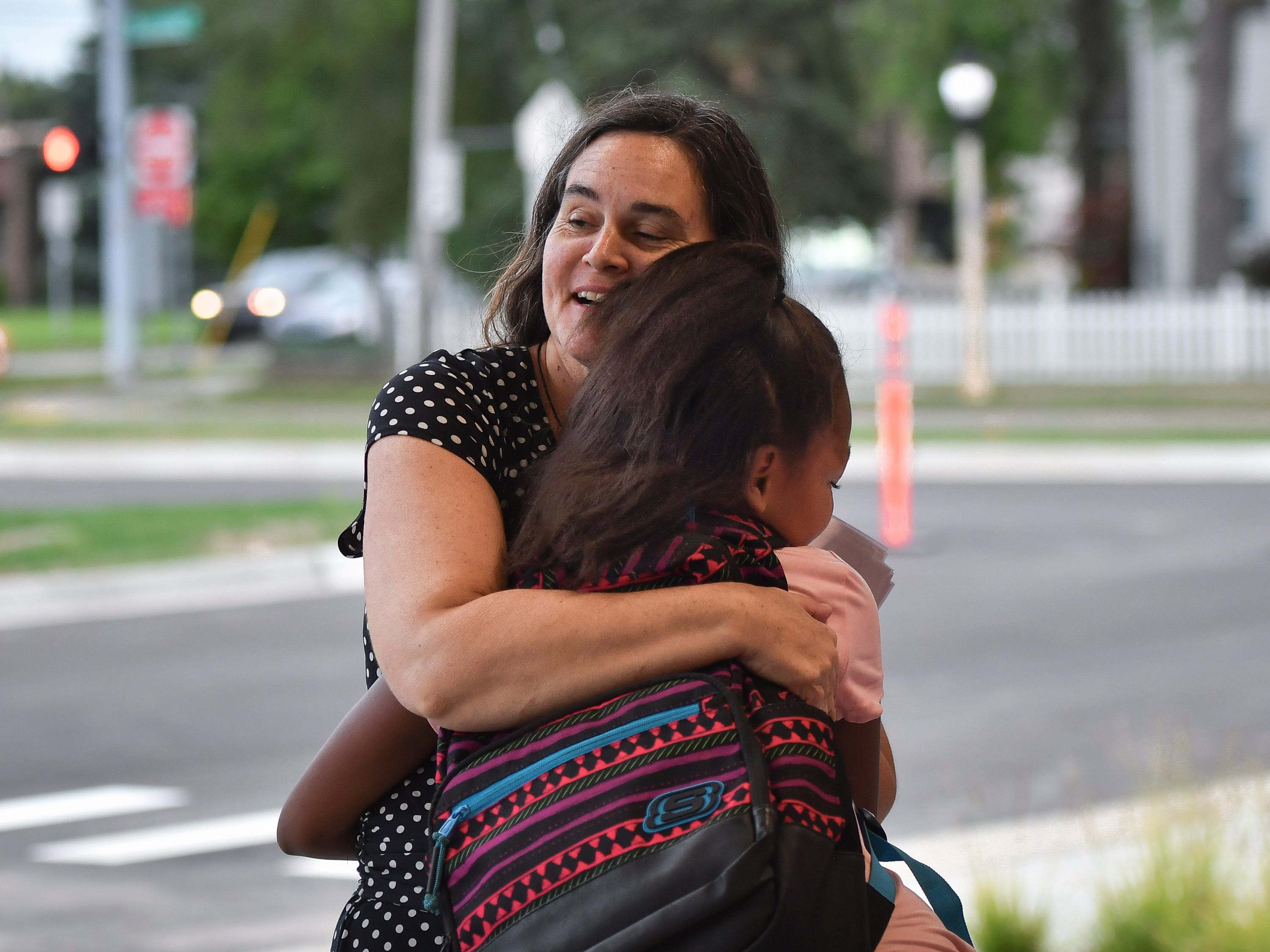 Fifth-grader Nataya Lewis hugs her former teacher Shannon Norris Monday morning, Aug. 27, 2018, during the first day of school at the newly reopened Pattengill Biotechnical Magnet School.