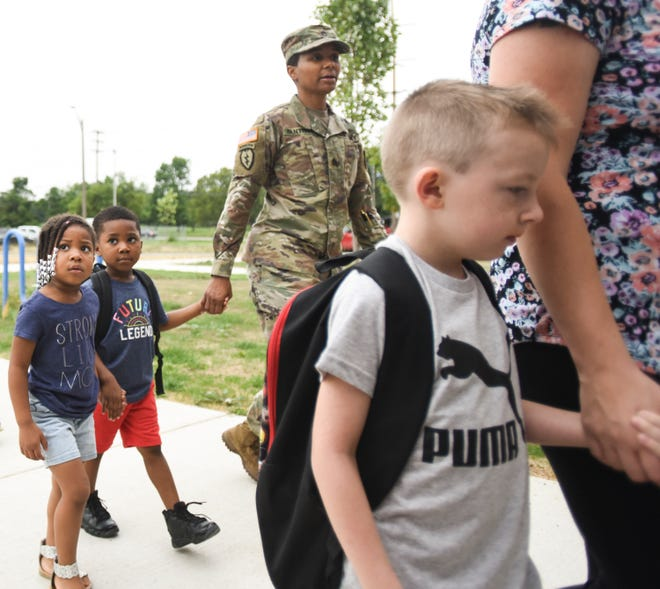 Romesa Fantroy, middle, holds her son Stephen's hand as she and daughter Nyla, 3, walk with him to his first day of kindergarten, Monday, Aug. 27, 2018, at the newly opened Pattengill Biotechnical Magnet School in Lansing.