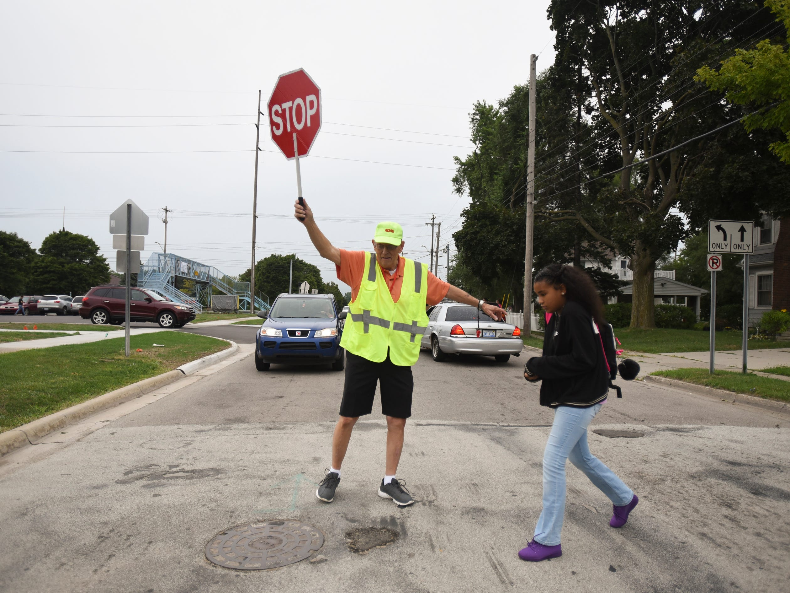 Crossing guard Jim Alrick of DeWitt helps a Pattengill Biotechnical Magnet School student cross the street Monday morning, Aug. 27, 2018.