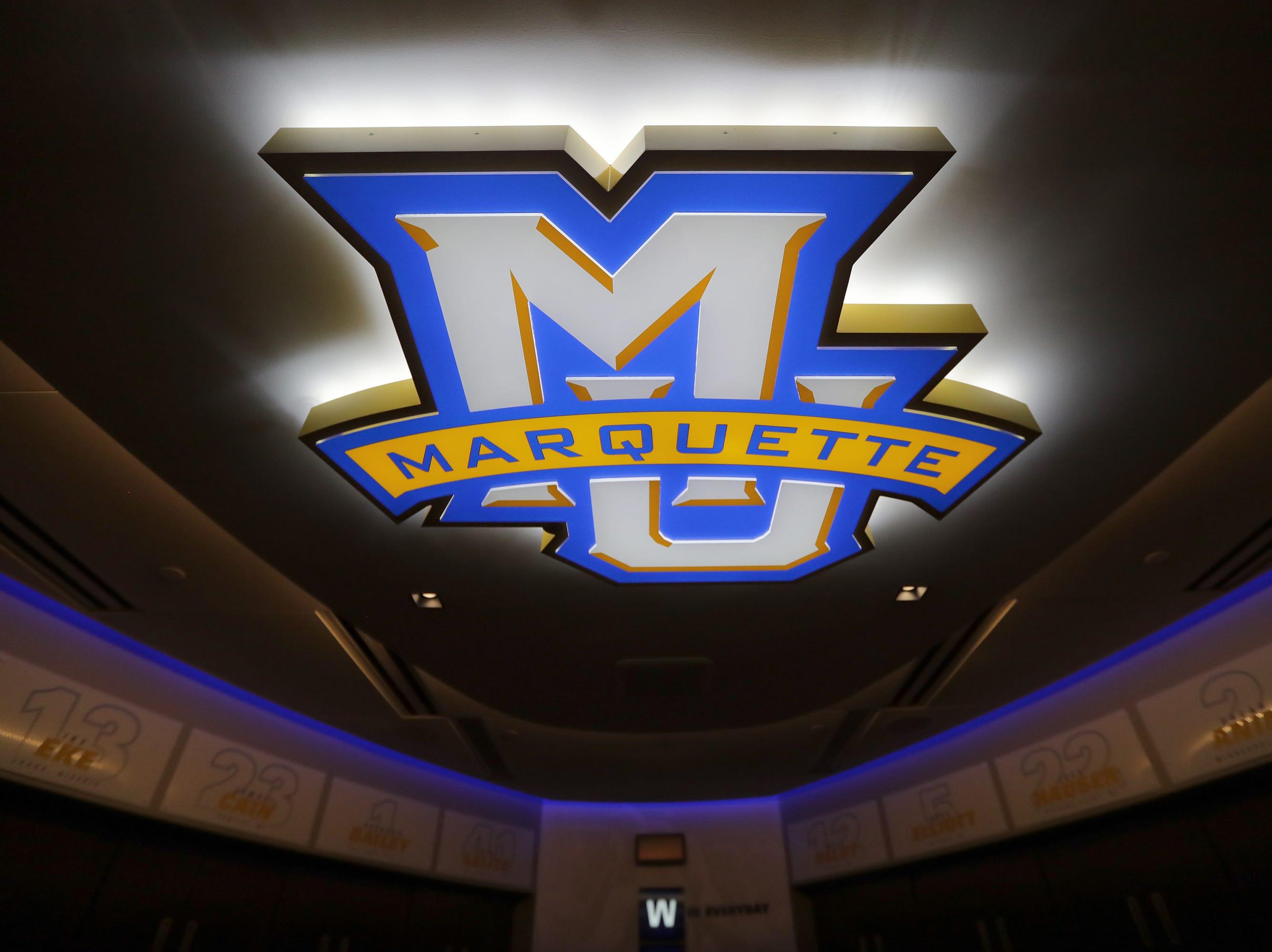 A bright Marquette logo adorns the new Marquette mens' basketball team locker room at the Fiserv Forum.
