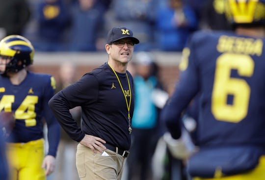 FILE - In this Nov. 25, 2017, file photo, Michigan coach Jim Harbaugh watches players warm up for an NCAA college football game against Ohio State in Ann Arbor, Mich. Harbaugh is 28-11 since taking over the Wolverines. That's a clear improvement from where Michigan was, but a bit underwhelming considering the hype and expectations that accompanied Harbaugh's arrival. Specifically, the Wolverines have struggled against their biggest rivals, going 1-5 against Ohio State and Michigan State. Michigan opens this season at Notre Dame. (AP Photo/Carlos Osorio, File) ORG XMIT: NY156
