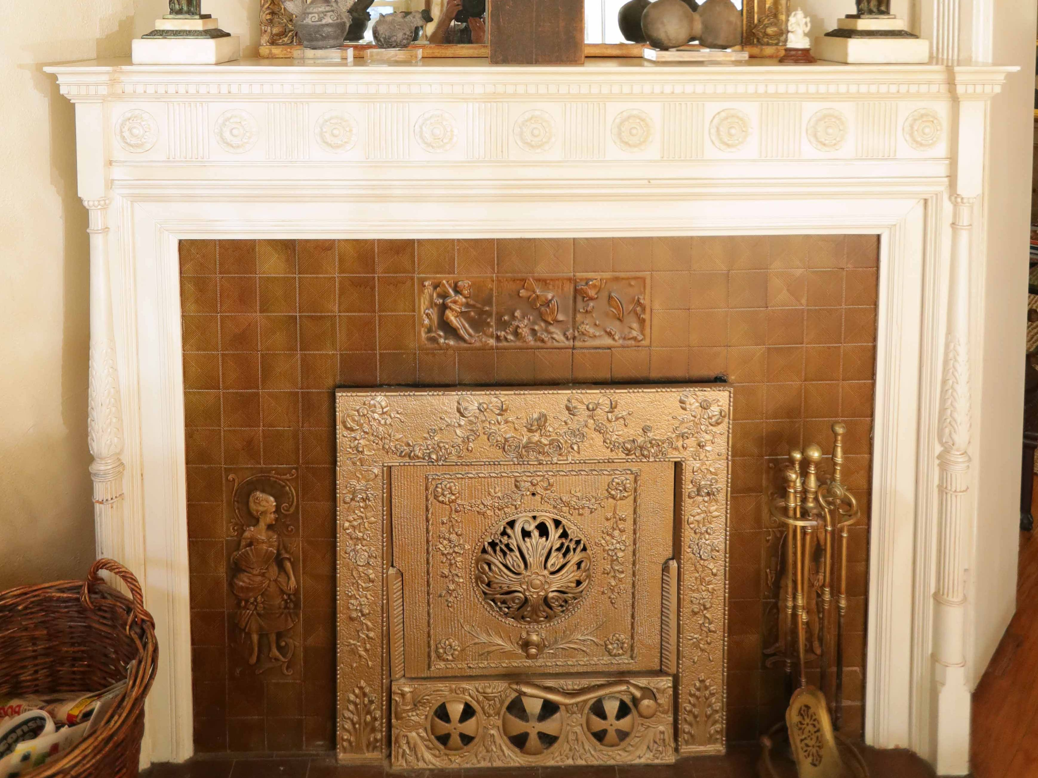 The working fireplace in the front parlor is surrounded by ceramic tile with a decorative steel plate covering and wooden mantel.