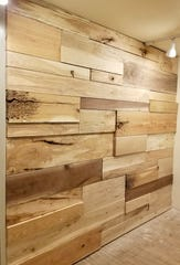 An accent wall showing different species of wood includes a hickory slab oozing with character caused by ant damage in the upper left area at the Urban Wood Lab in West Allis.