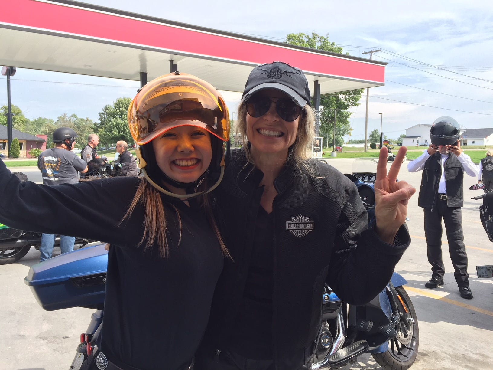 Karen Davidson greets a rider from Osaka, Japan during a stop for gas in Brookfield, Mo. A group of international riders from several countries joined the Southwest leg of the Harley-Davidson 115th anniversary ride in Oklahoma City. They will travel to Milwaukee.