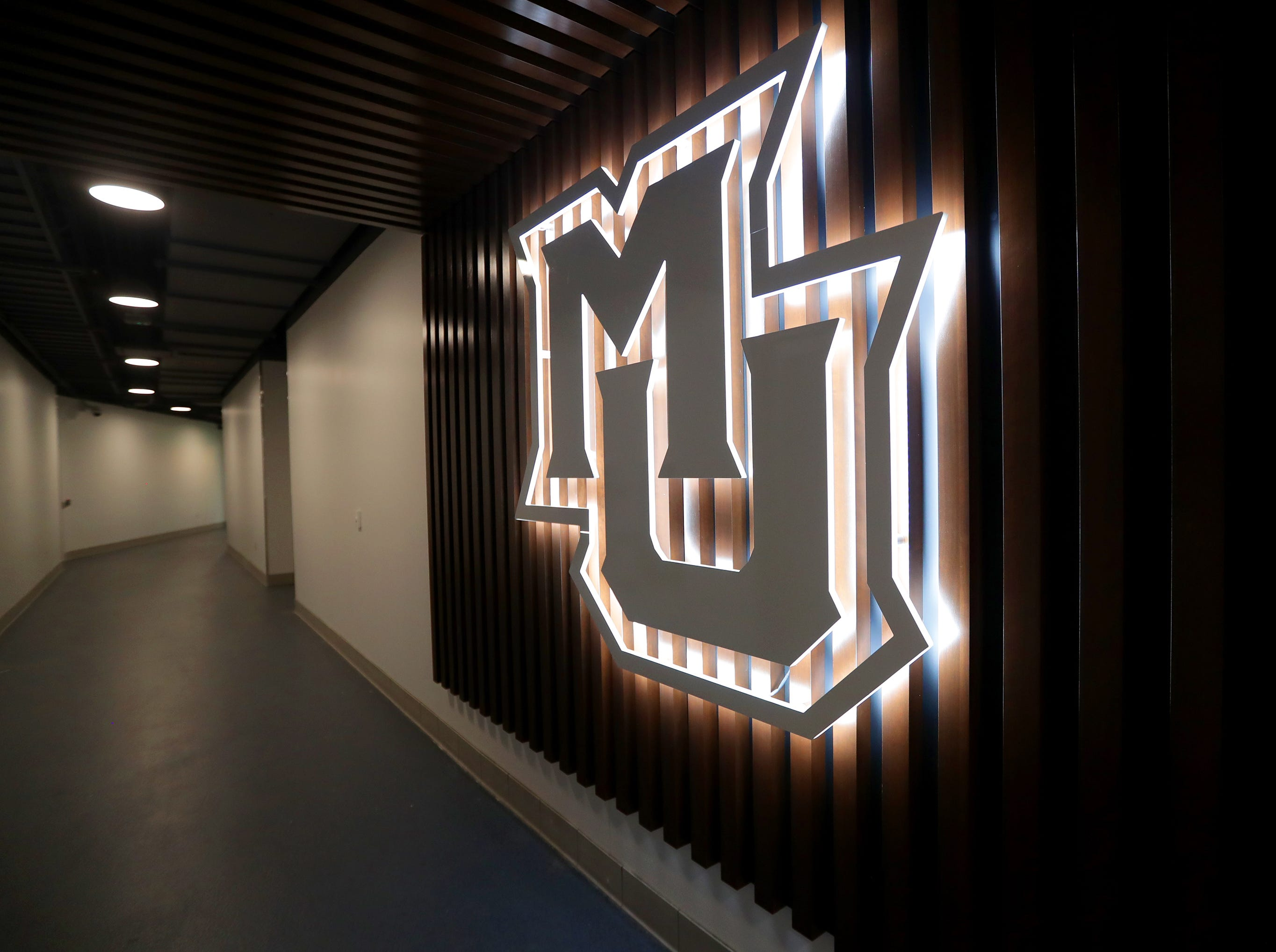 """A glowing """"MU"""" sign lights up the hallway outside the Marquette locker room. The Marquette mens' basketball team locker room is complete at the new Fiserve Forum, the home of the Milwaukee Bucks. Monday, August 27, 2018.  -  Photo by Mike De Sisti / Milwaukee Journal Sentinel"""