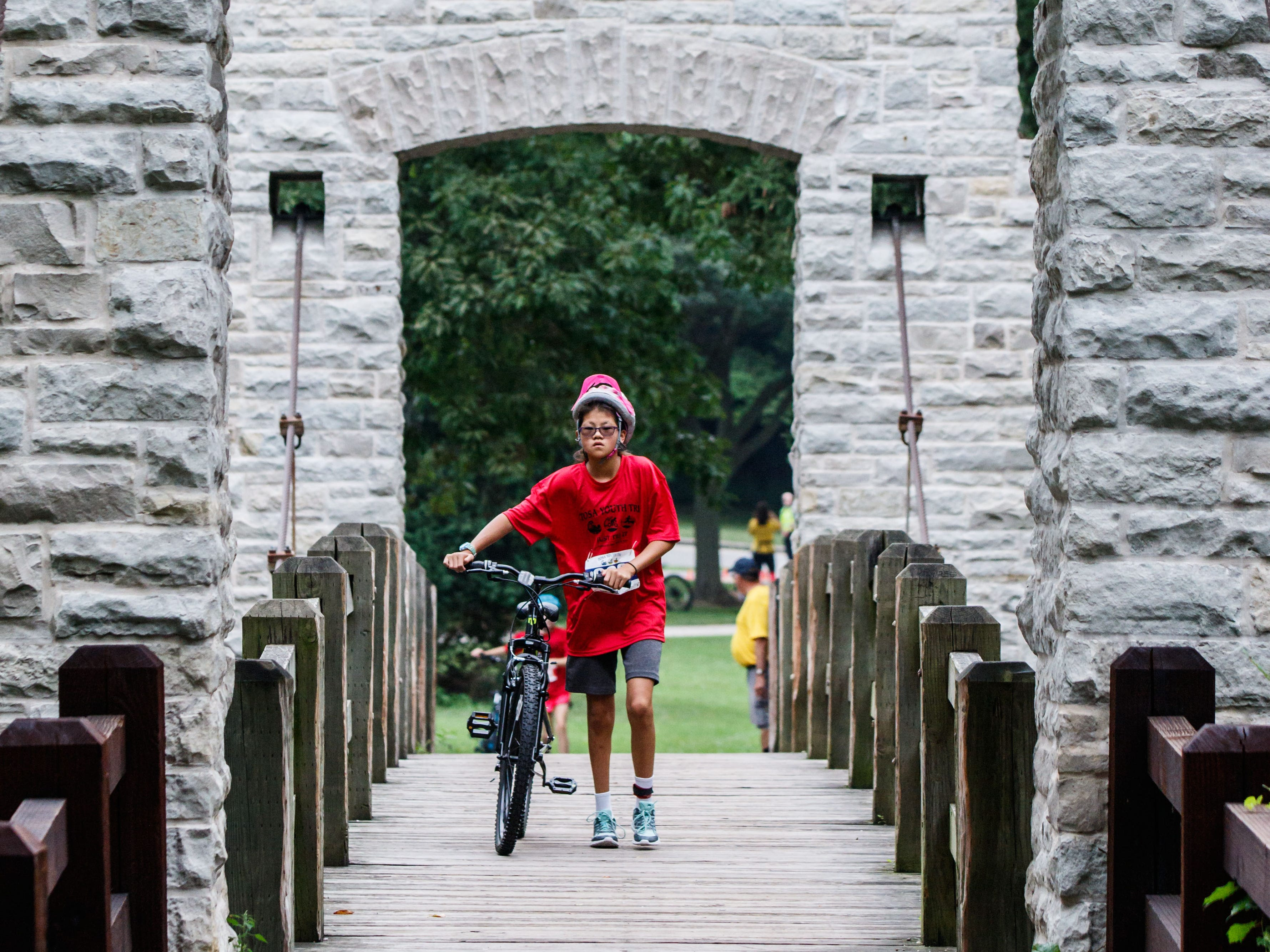 Competitors return from the cycling segment of the third annual TOSA Youth Tri at Hoyt Park in Wauwatosa on Saturday, August 25, 2018. The fundraiser, hosted by Friends of Hoyt Park & Pool, is USA Triathlon sanctioned and features both fun and challenge races for various age groups.