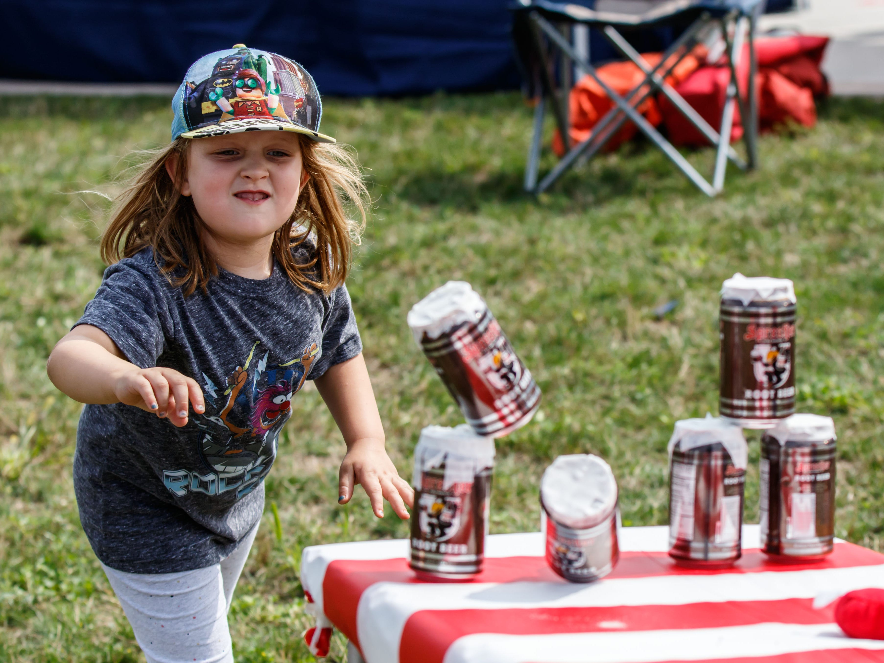 Four-year-old Emi Stuck of Glendale knocks over a stack of root beer cans during the second annual Root Beer Bash at Richard E. Maslowski Community Park in Glendale on Saturday, August 25, 2018. The free event, hosted by the City of Glendale and Sprecher Brewing Company, features root beer themed food, games, live music and more.