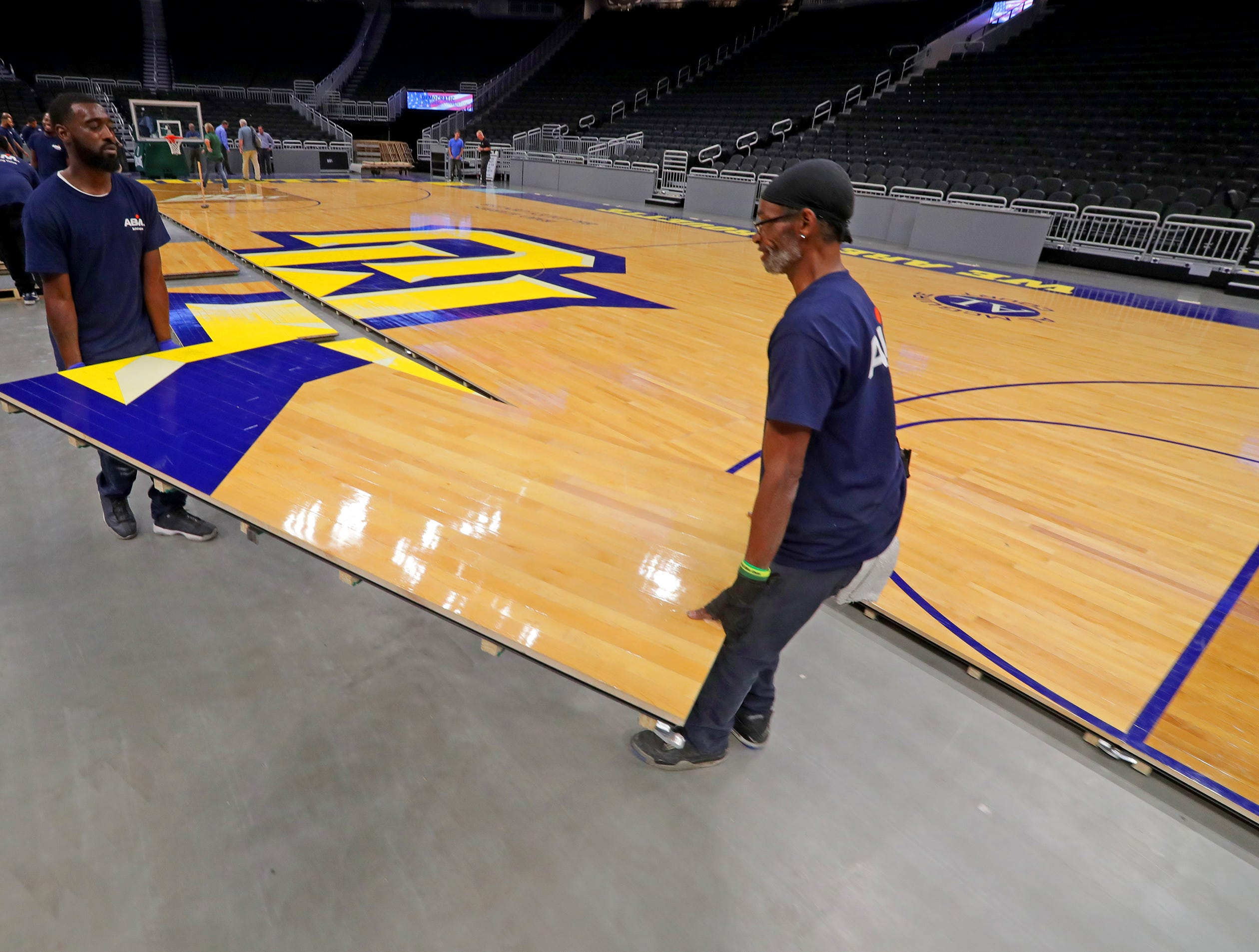 Byron Powell (right) and Broderick Jordan work to install the Marquette floor. The Marquette mens' basketball team locker room is complete at the new Fiserve Forum, the home of the Milwaukee Bucks. Monday, August 27, 2018.  -  Photo by Mike De Sisti / Milwaukee Journal Sentinel
