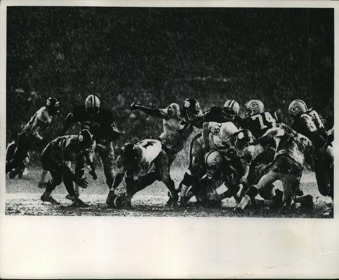 """The Green Bay Packers and Pittsburgh Steelers battle it out in the rain at County Stadium on Aug. 31, 1968. The Packers beat the Steelers, 21-17, in the fifth exhibition game of the season under Green Bay's new coach, Phil Bengston. Milwaukee Journal and Sentinel photographer Heinz Kluetmeier won second place for the photo, titled """"American Gladiators,"""" in the sports category in the national Pictures of the Year competition. The photo was published several times, including in the March 2, 1969, Milwaukee Journal."""