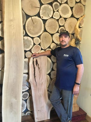 Arborist and Hoppe Tree Service president August Hoppe stands with live-edge timber next to a striking accent wall using rounds from trees that once grew nearby.