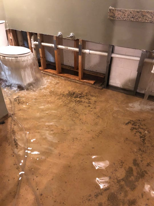 Waste water gushes out of the Stallmann family's basement toilet for the second time in a week. Fox Point and other North Shore communities are bailing out from a heavy rain storm Sunday.