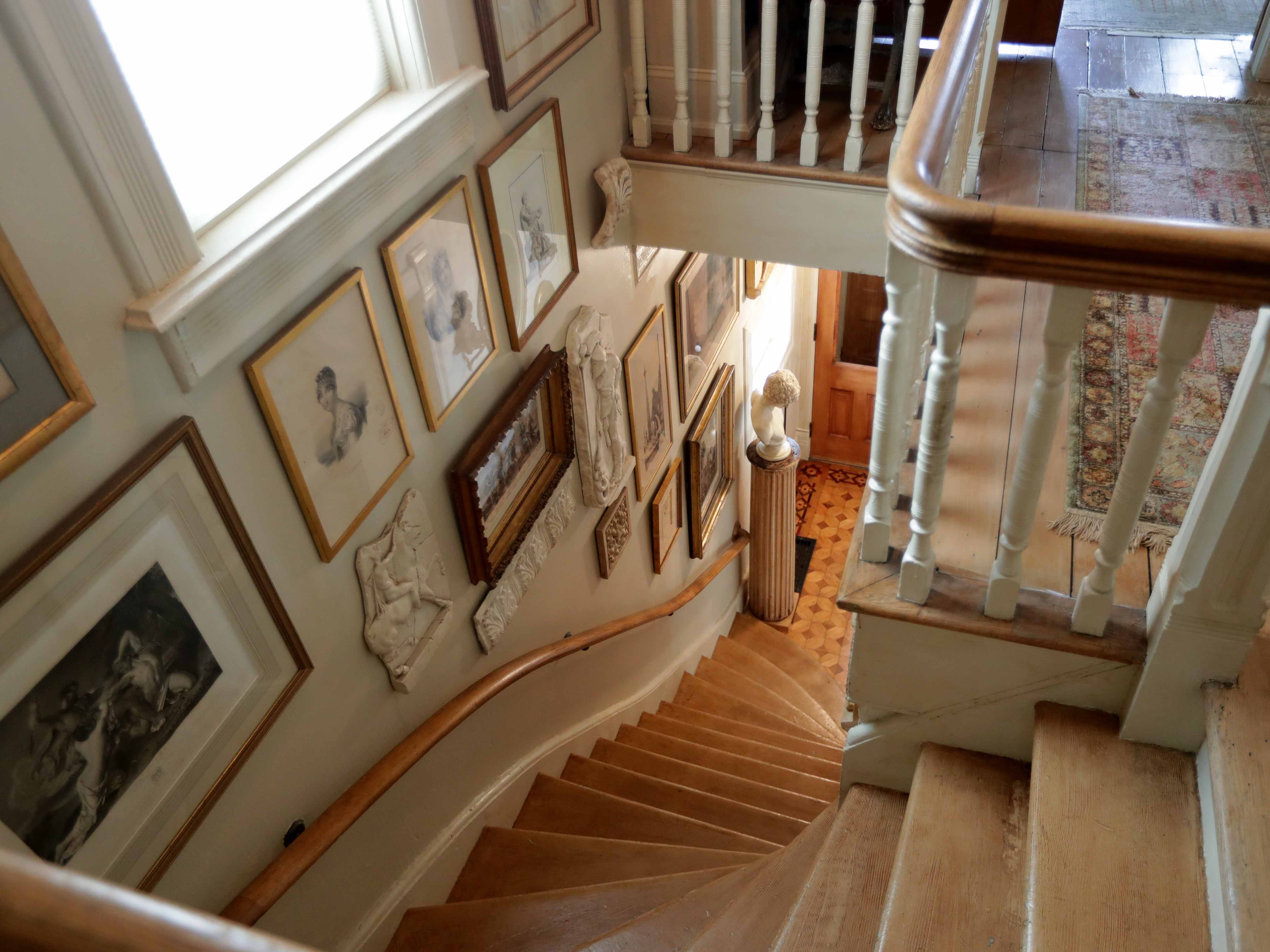 A curved wooded staircase leading to the second floor is loaded with art.
