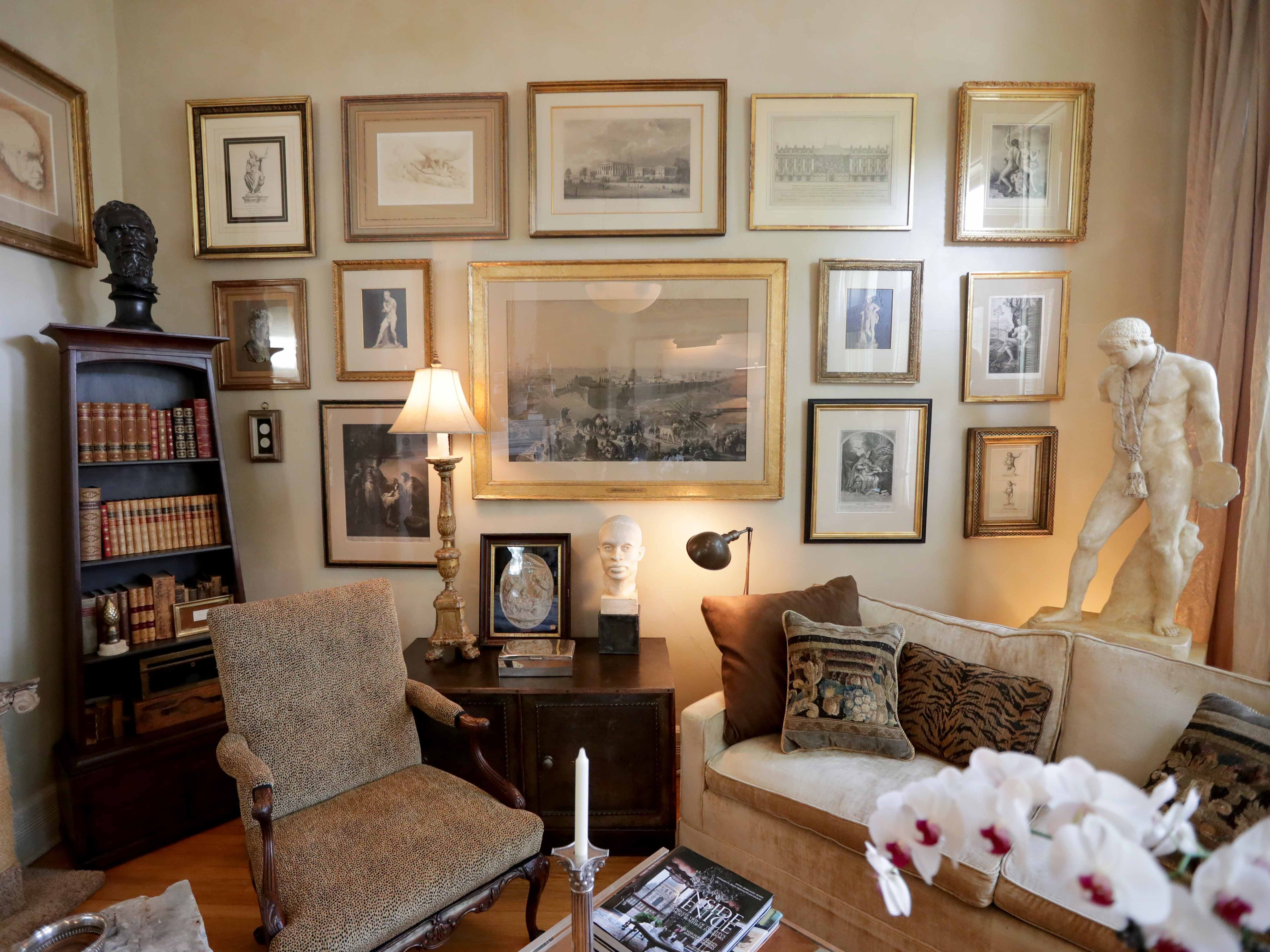 Framed artwork fills this wall in the front parlor. The owner likes to use antique frames.