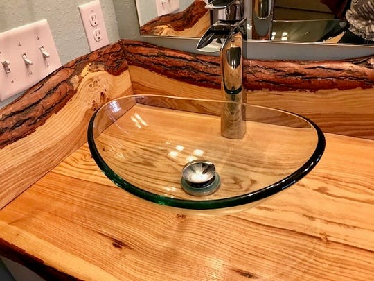 The grain in a honey locust wood counter top shows through the glass sinks in Susan Kizaric's bathroom.