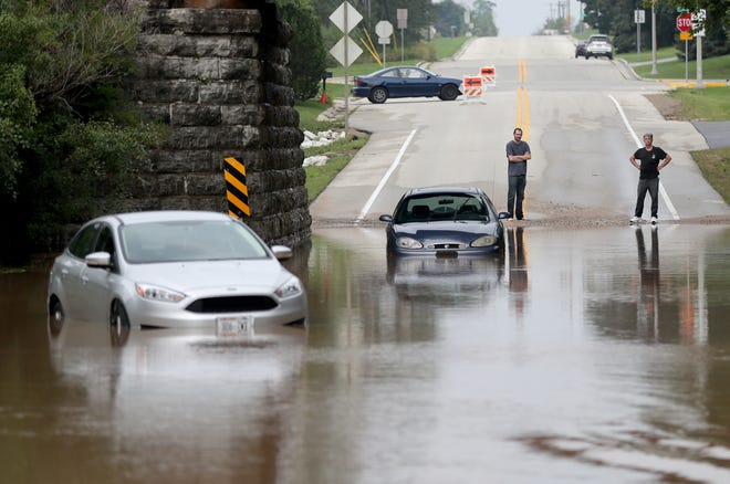 Jim Grant (right) of Milwaukee and Darryl Cain of Hartford stand on a closed road as their cars are both stranded in water on Sunset Road just off Highway 32 in Port Washington on Monday. The two were headed to work before dawn at the nearby KMC Stamping in Port Washington and were unable to see the flooding.
