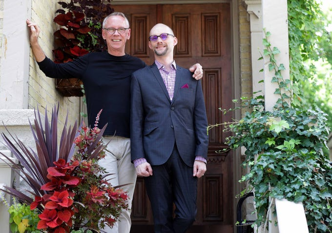 Gene Berube (left) and his partner, Matthew Neu, stand on the porch of their home.