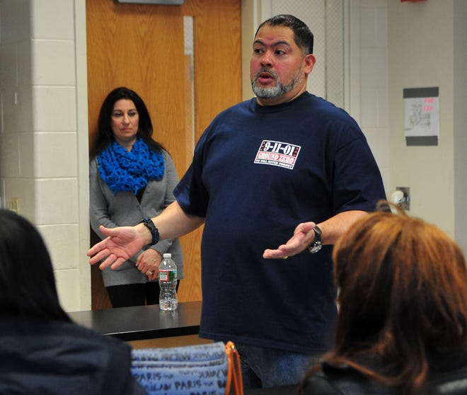 Allison Jimeno listens as her husband Will talks to students. Retired Port Authority Police officer Will Jimeno talks to 6th graders at Black River Middle School about being Sept. 11, 2001, being trapped under the World Trade Center, and how he was resuced. Chester Township, NJ. Feb. 27, 2014. Special to NJ Press Media/Karen Mancinelli/Daily Record MOR 0303 Chester 911