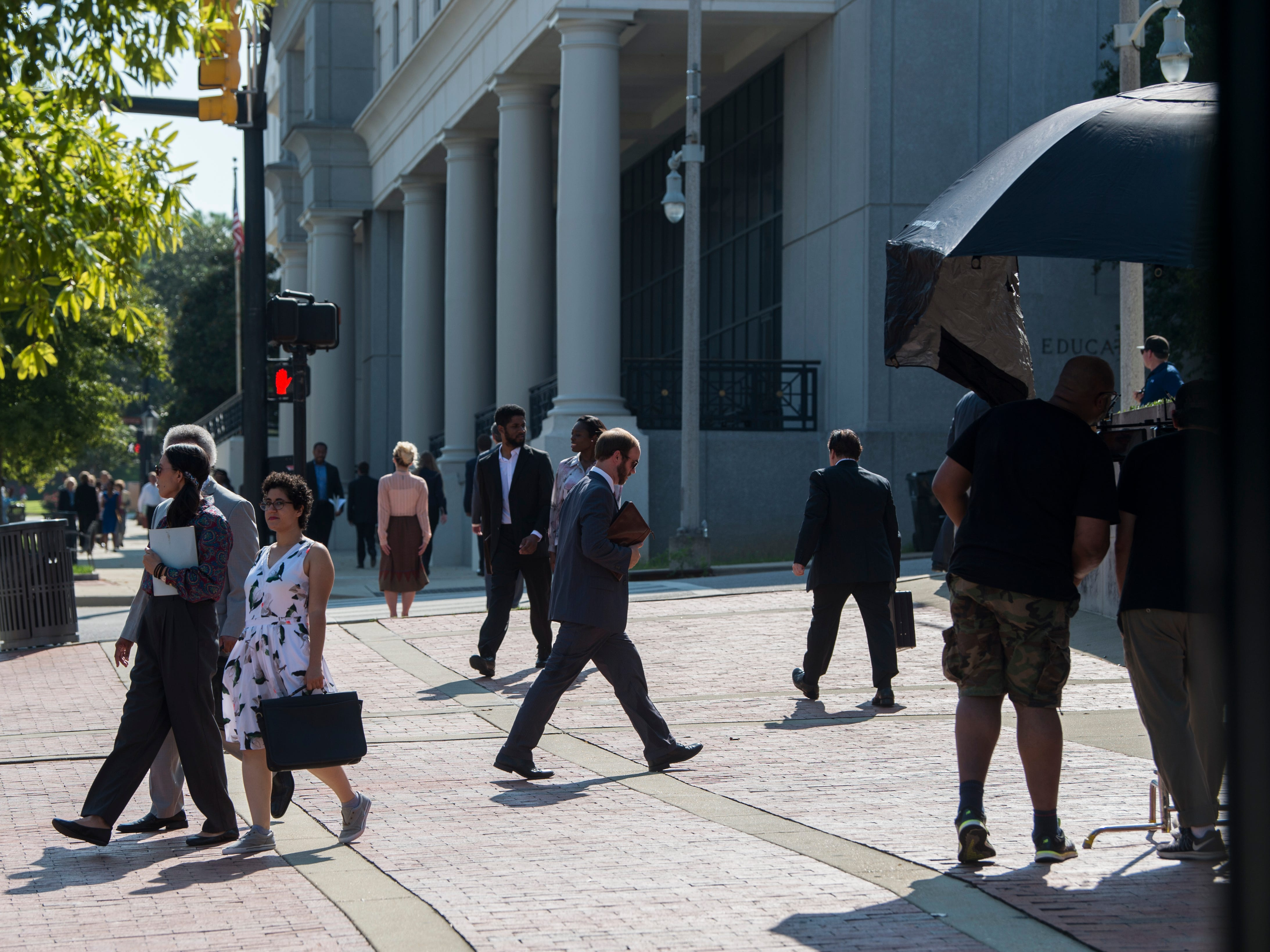 Extras walk through the sidewalks during the filming of 'Just Mercy' at the intersection of Dexter Ave. and Hull Street in Montgomery, Ala., on Monday, Aug. 27, 2018.