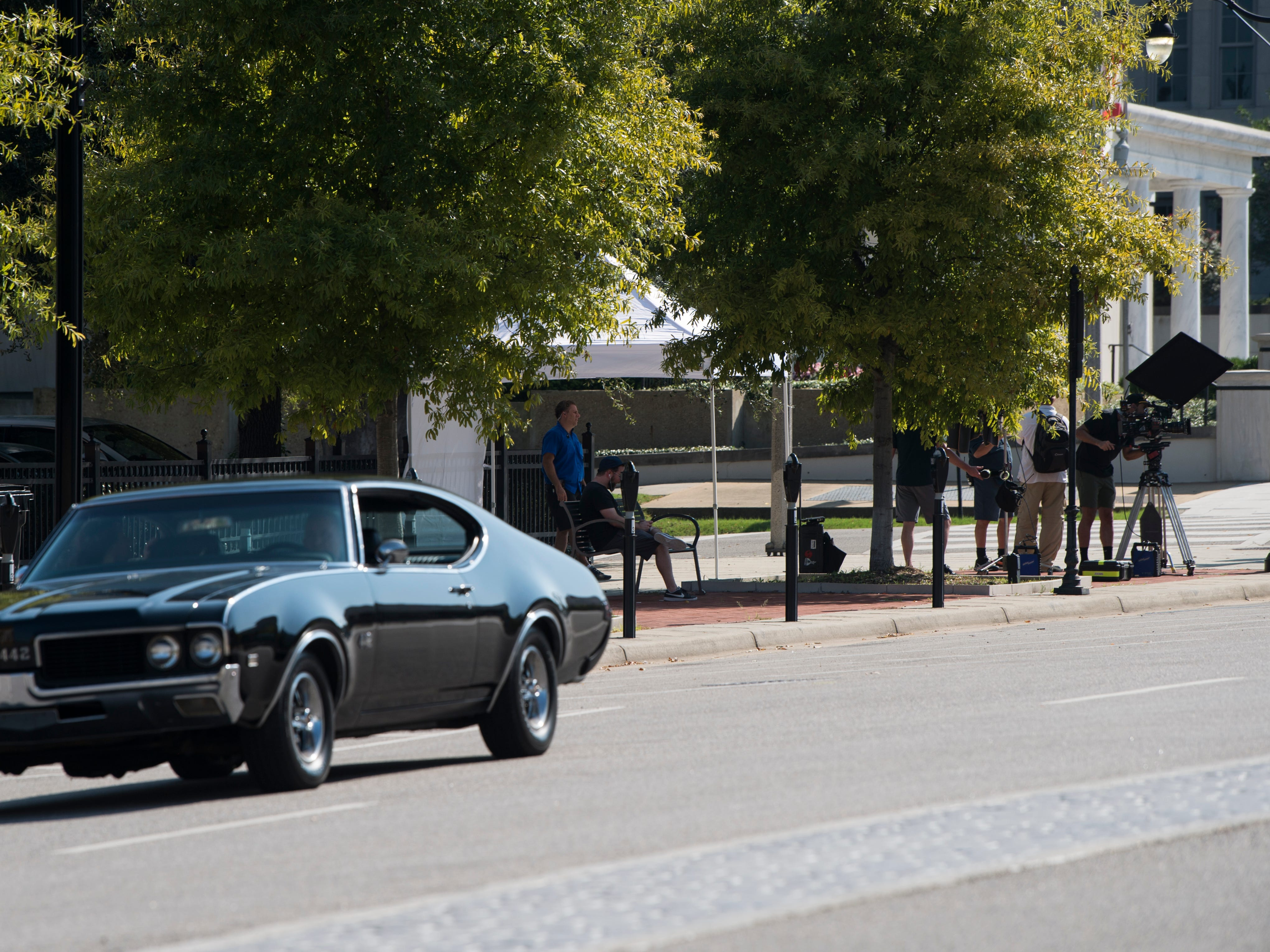 Cars from the 1990's line the street as crews film scenes for 'Just Mercy' at the intersection of Dexter Ave. and Hull Street in Montgomery, Ala., on Monday, Aug. 27, 2018.