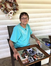 Carolyn Till, 66, sitting on her front porch, looking at old photographs of her daddy on Monday, June 27.