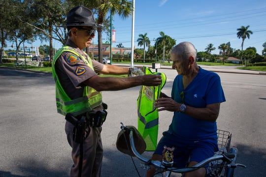 Florida Highway Patrol Trooper David Rodriguez, left, gives a free safety vest to Armando Morages during Operation Pedestrian Education and Developing Safety at the parking lot near the corner of U.S. 41 and Shadowlawn Drive in Collier County on Monday, Aug. 27, 2018. The purpose of the operation was to decrease the number of injuries and deaths through education and enforcement, focusing on areas prone to pedestrian- and bicyclist-involved crashes.