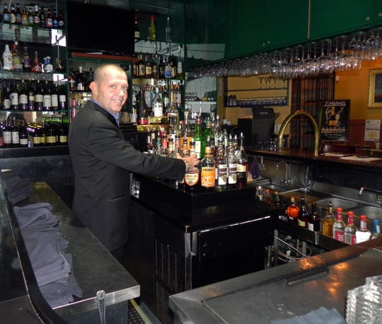 Ty Ernst, owner of T-Michael's Steak & Lobster House, at his restaurant's bar with daily happy hours on Venetian Bay in Naples.