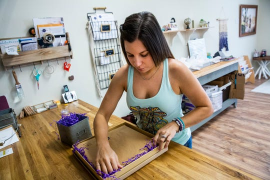 Edie Paterson packages a finished wedding album for a client at the Neubek Photographers work space in Naples on Monday, August 27, 2018.
